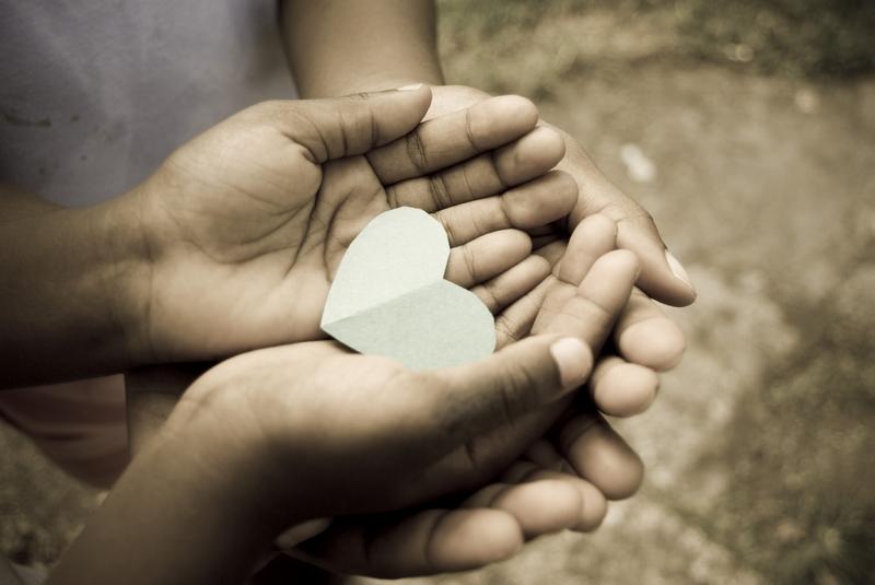 love; beautiful hands of children holding green heart shape